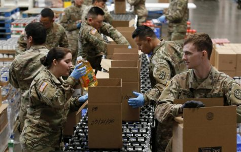 Members of 115th Regional Support Group of the California National Guard load boxes with food at the Sacramento Food Bank and Family Services in Sacramento, Calif., Saturday, March 21, 2020.
