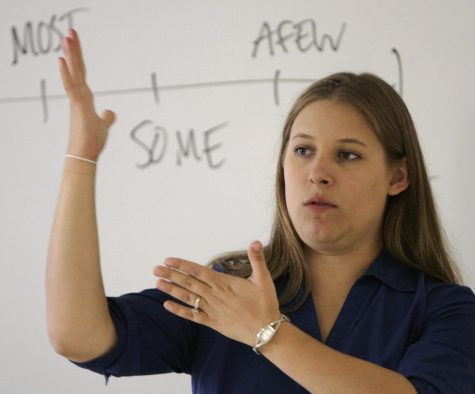 A high school teacher gives instruction to her class in sign.