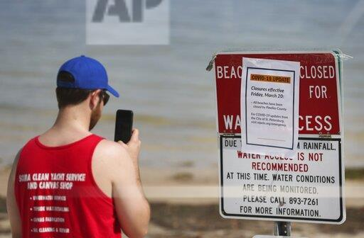 Zac Giparas, 28, takes a picture of the Covid-19 update beach closure sign along the sand at North Shore Park on March 20, 2020 in St. Petersburg. Giparas is a USF grad student currently on spring break.