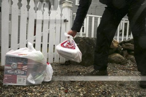 Photo courtesy of AP Images. Instacart worker leaves groceries at the gate of a home in East Derry, N.H.