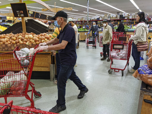 Several customers at Super King Markets grocery store wear face masks and gloves Friday, April 3, 2020, in Los Angeles, as protection against the coronavirus.(AP Photo/Damian Dovarganes)