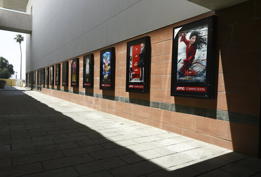 Posters for upcoming movies are displayed in an empty corridor at the currently closed AMC Burbank Town Center 8 movie theaters complex, Wednesday, April 29, 2020, in Burbank, Calif. (AP Photo/Chris Pizzello)