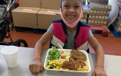 Photo Courtesy of Martha's Village & Kitchen. Resident child picking up a meal.